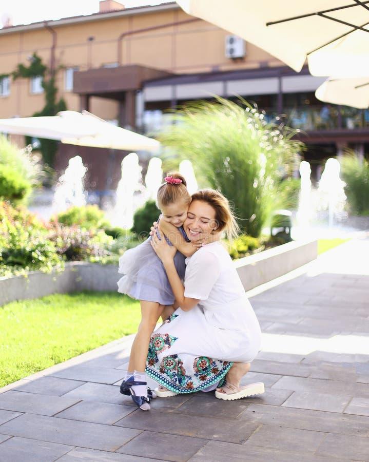 Pequeña situación bonita caucásica de la muchacha con la madre en yarda y vestido gris que lleva fotografía de archivo