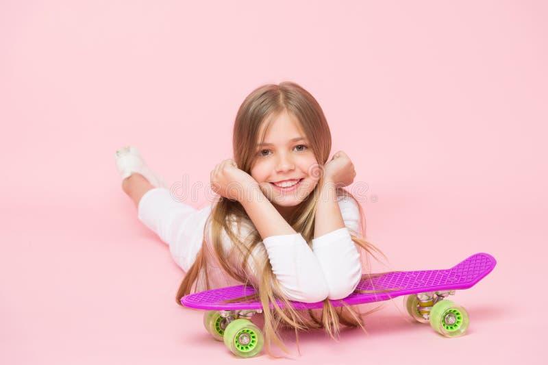 Pequeña sonrisa de la muchacha con el tablero del patín en fondo rosado Patinador del niño que sonríe con longboard Mentira del n imagen de archivo