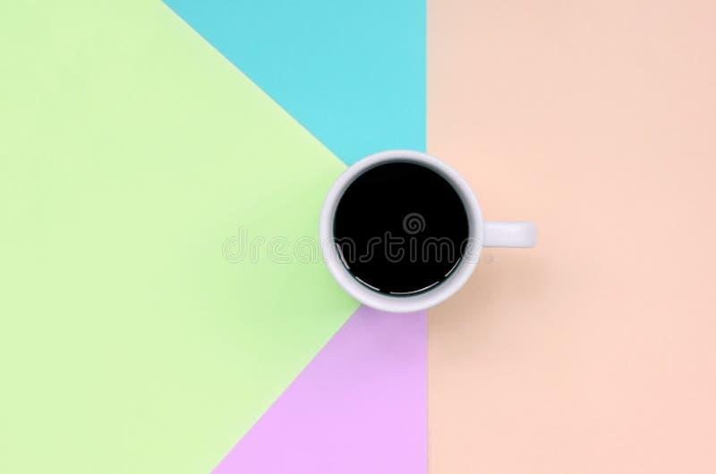 Pequeña taza del café con leche en el fondo de la textura del papel rosado de la moda, azul, coralino y de la cal en colores past foto de archivo libre de regalías