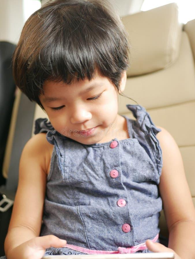 Pequeña tenencia asiática del bebé y usar un teléfono móvil, mientras que se sienta en un coche de conducción fotografía de archivo libre de regalías
