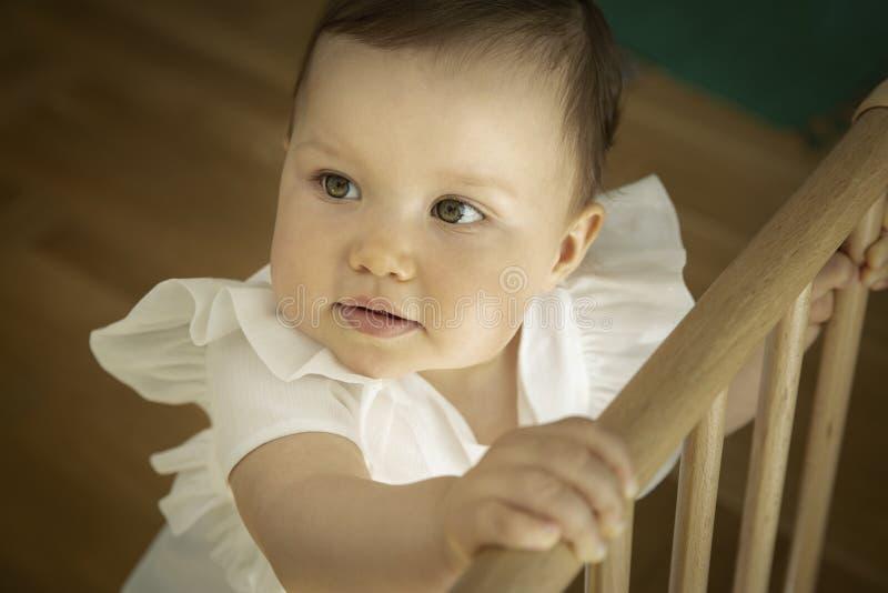 Pequeña tenencia del bebé sobre el top de la puerta de la seguridad fotos de archivo