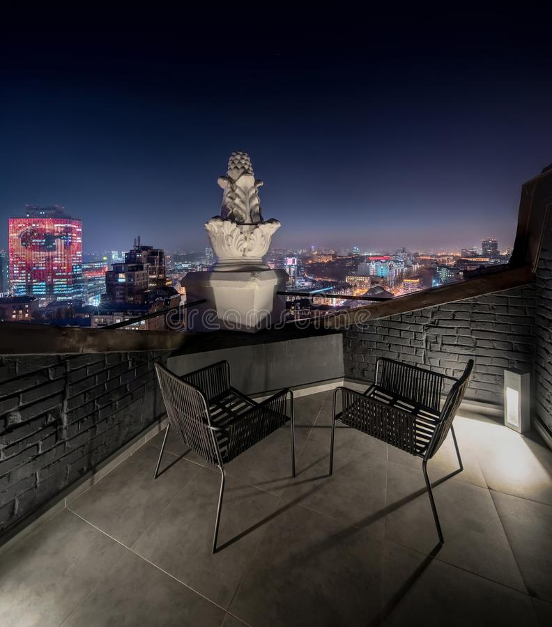 Pequeña terraza con las paredes de ladrillo en fondo del paisaje urbano de la noche foto de archivo