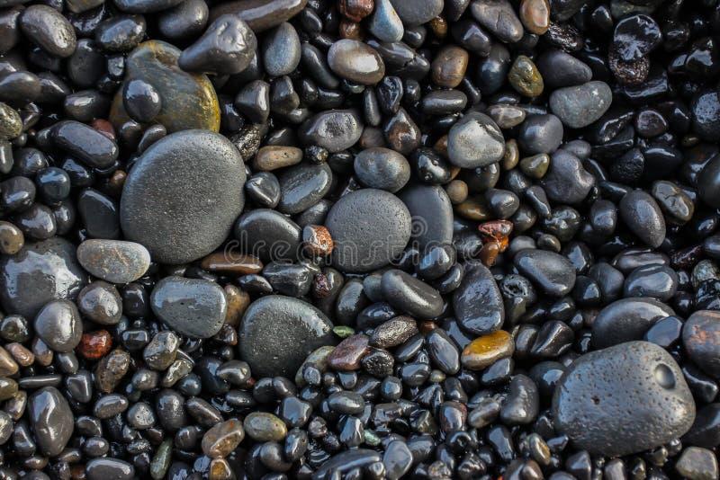 Pequeña textura volcánica de las piedras de la costa fotos de archivo