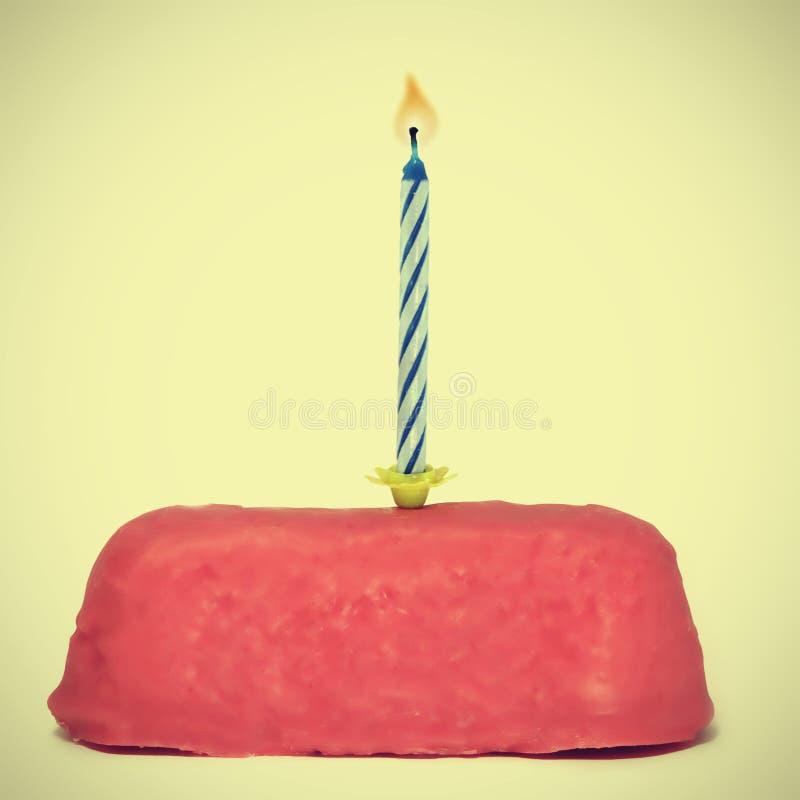 Pequeña torta de cumpleaños con la vela imagenes de archivo