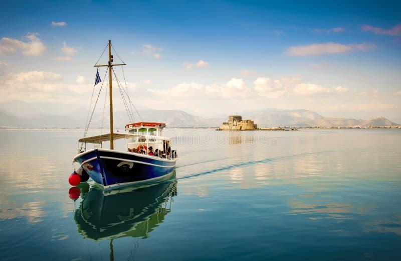 Pequeña transferencia de madera del barco al grupo de turistas a la isla de Bourtzi una prisión antigua Nafplion, Grecia foto de archivo libre de regalías