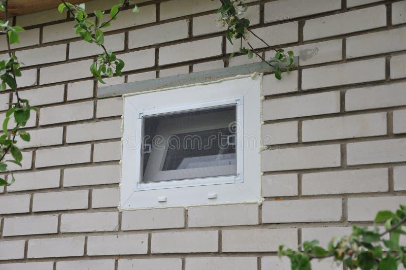 Peque?a ventana del metal-pl?stico con el ladrillo blanco de la red de mosquito en la pared al lado de las ramas de Apple foto de archivo libre de regalías