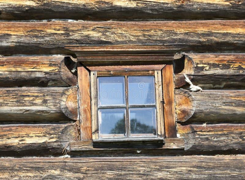 Pequeña ventana vieja con el vidrio con un cielo azul en el fondo de la pared de madera de la cabaña de madera del campo fotografía de archivo
