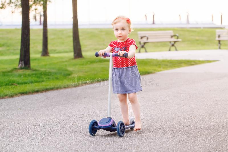 pequeña vespa activa del montar a caballo de la niña pequeña en el camino en parque al aire libre el día de verano imagenes de archivo