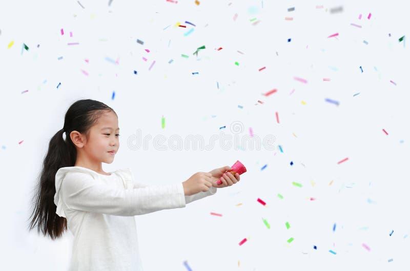 Pequeña y adorable niña asiática que dispara popper confetti sobre fondo blanco con espacio para copiar fotografía de archivo libre de regalías