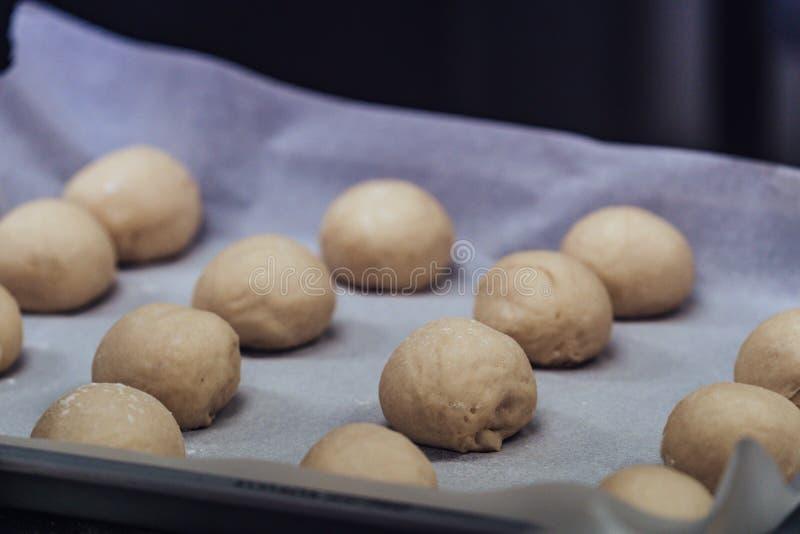 Pequeñas bolas de la pasta de pan colocadas en cocinar el documento sobre la cacerola - lista para ser cocido, sistema de la coci fotografía de archivo