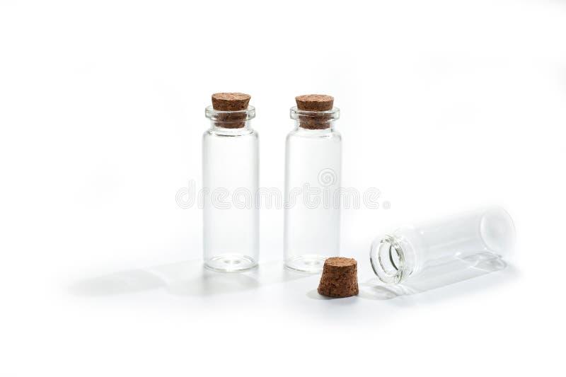Pequeñas botellas de cristal con la tapa del corcho en el fondo blanco foto de archivo libre de regalías