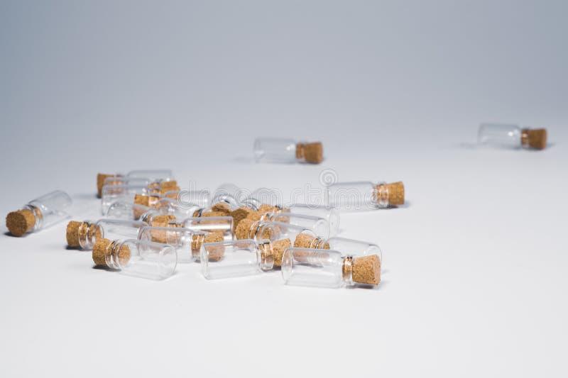 Pequeñas botellas vacías con el tapón del corcho aislado en blanco Buques de cristal envases transparentes Tubos de prueba imagenes de archivo