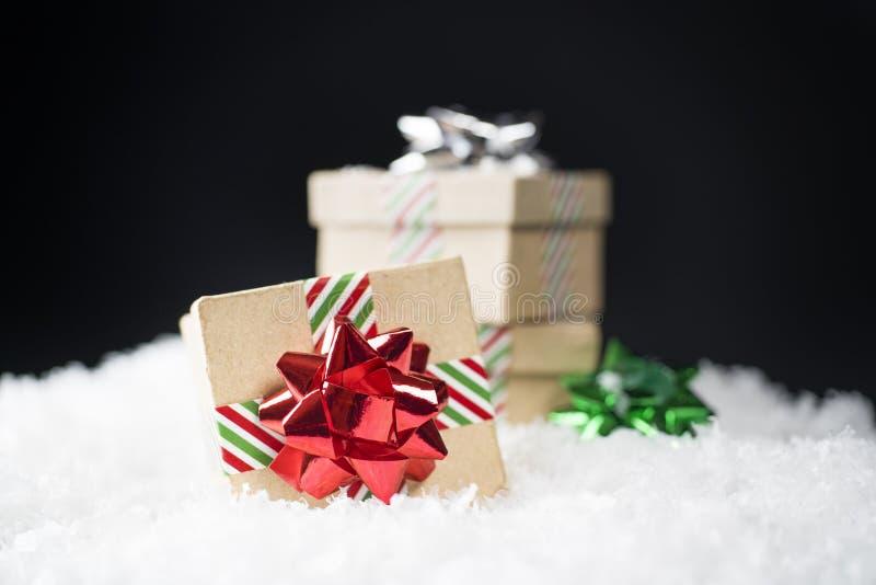 Pequeñas cajas de regalo de la cartulina con los arcos brillantes del día de fiesta y r rayado foto de archivo