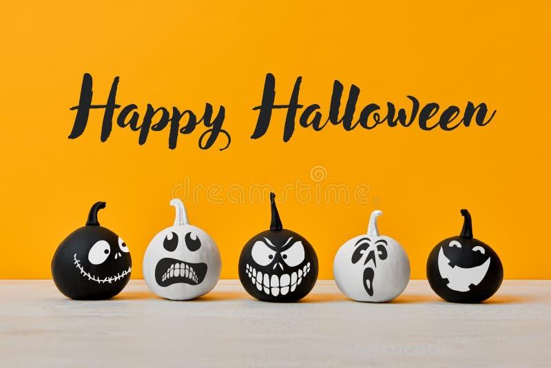 Pequeñas calabazas blancos y negros lindas de Halloween con las expresiones faciales divertidas que se colocan de lado a lado en  imagen de archivo libre de regalías