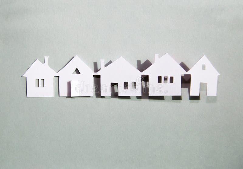 Pequeñas casas de pueblo seguidas. Concepto de compra de propiedades y viviendas. Fondo de diseño de corte de papel. Fondo de di fotografía de archivo libre de regalías