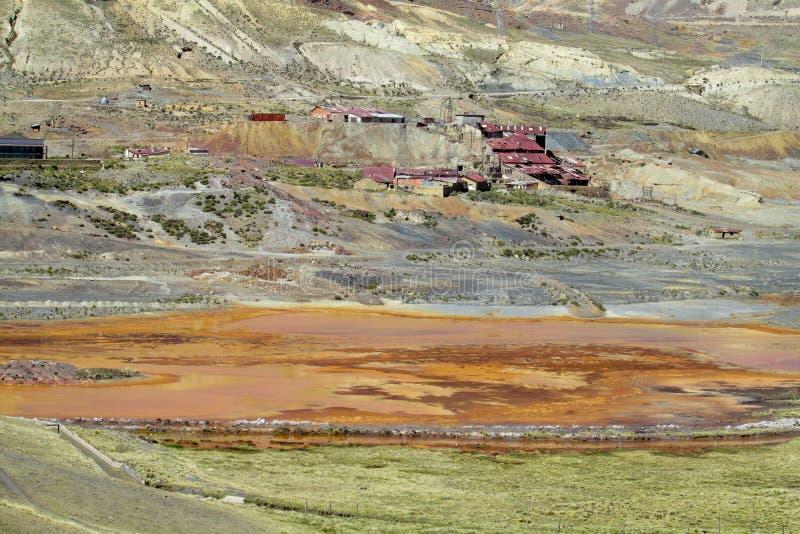 Pequeñas casas del pueblo con el lago contaminado cercano de los tejados rojos imagenes de archivo