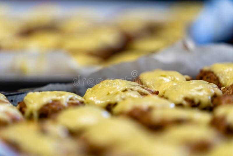 Pequeñas chuletas de la carne cubiertas con queso de fusión foto de archivo