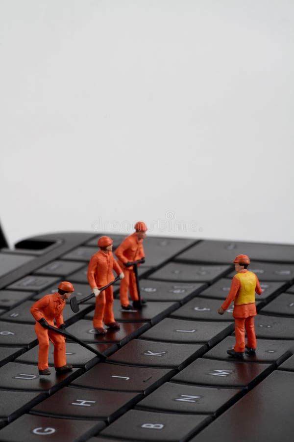 Pequeñas estatuillas de los trabajadores que reparan el teclado de ordenador imágenes de archivo libres de regalías