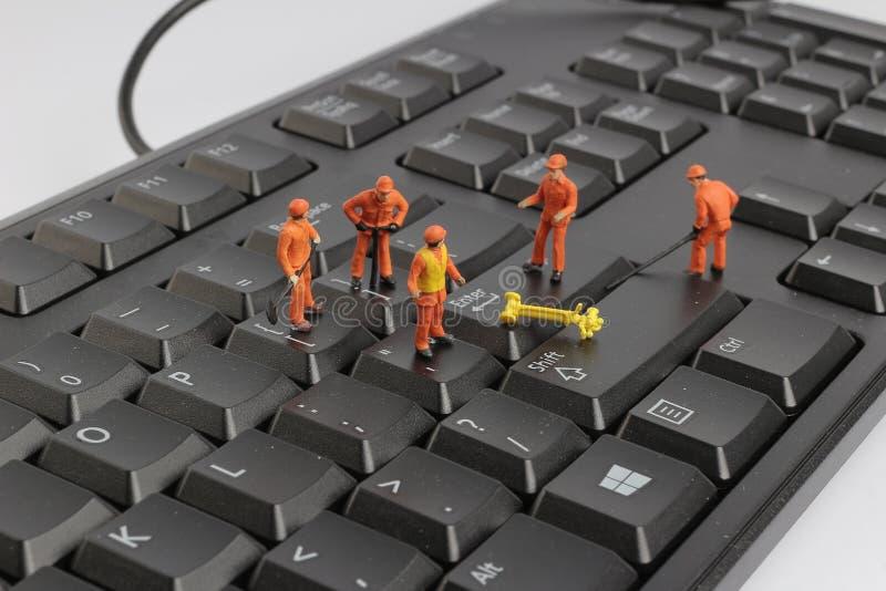 Pequeñas estatuillas de los trabajadores que reparan el teclado de ordenador fotos de archivo libres de regalías