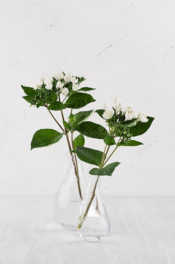 Pequeñas flores blancas en florero transparente en la tabla de madera blanca suave, vertical, decoración moderna del hogar de la  fotos de archivo