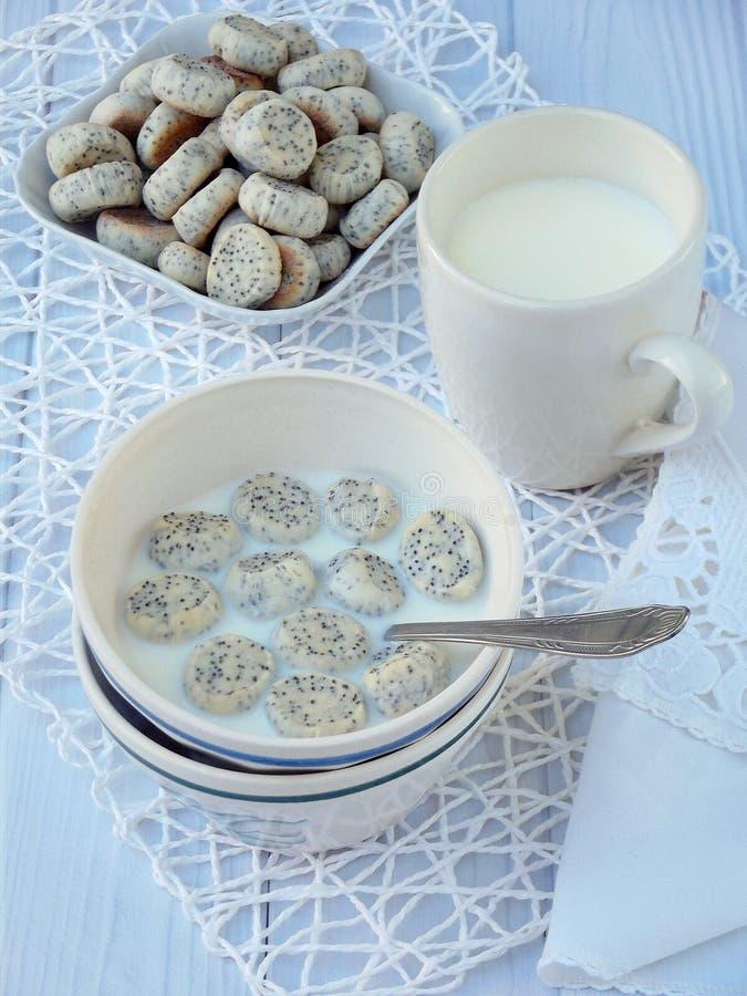Pequeñas galletas de la amapola con leche en un fondo ligero Galletas lituanas tradicionales de la Navidad Kuchykai Desayuno dulc fotos de archivo libres de regalías