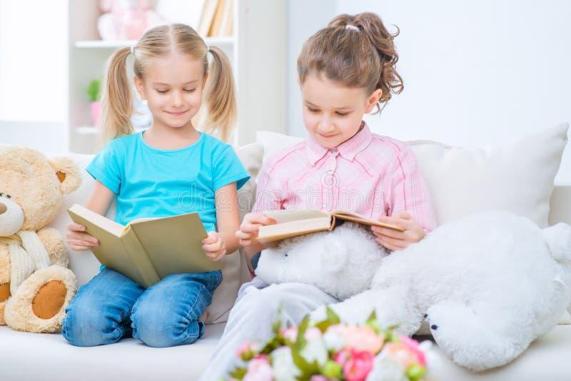 Pequeñas hermanas alegres que se sientan en el sofá foto de archivo libre de regalías