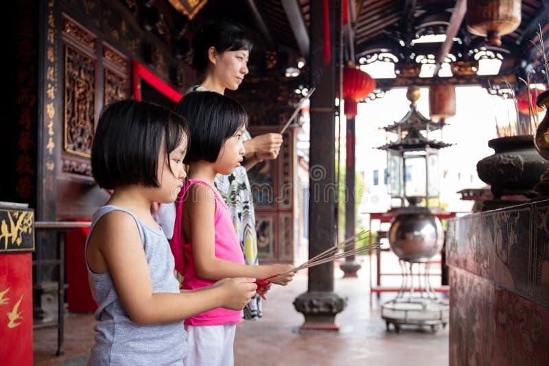 Pequeñas hermanas asiáticas y madre chinas que ruegan con los palillos ardientes del incienso imagen de archivo