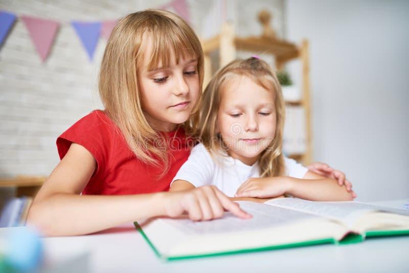 Pequeñas hermanas centradas en la lectura imágenes de archivo libres de regalías