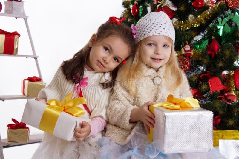 Pequeñas hermanas con los presentes debajo del árbol de navidad foto de archivo