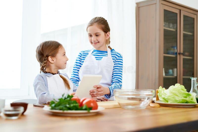 Pequeñas hermanas envueltas para arriba en cocinar fotografía de archivo