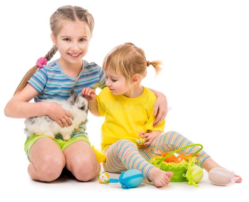 pequeñas hermanas felices con su conejo fotos de archivo