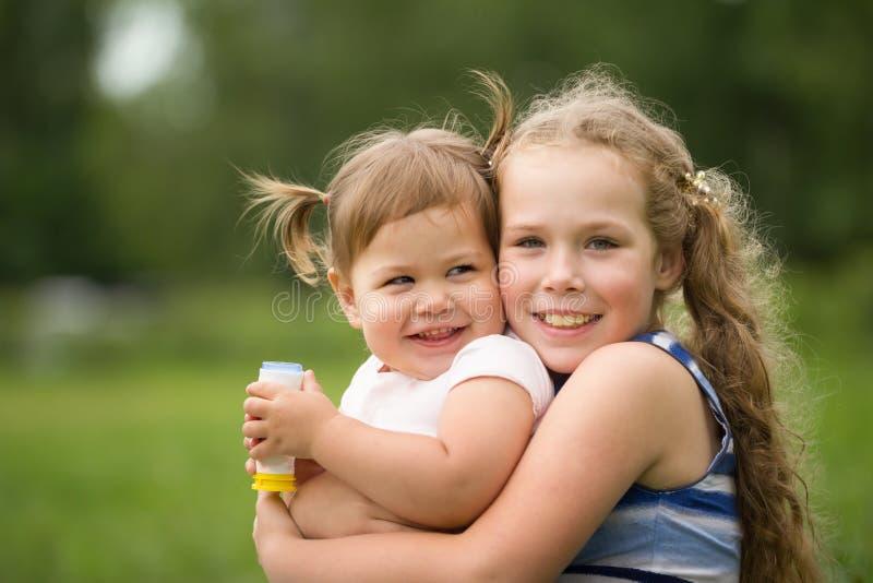 Pequeñas hermanas felices - retrato en parque fotos de archivo