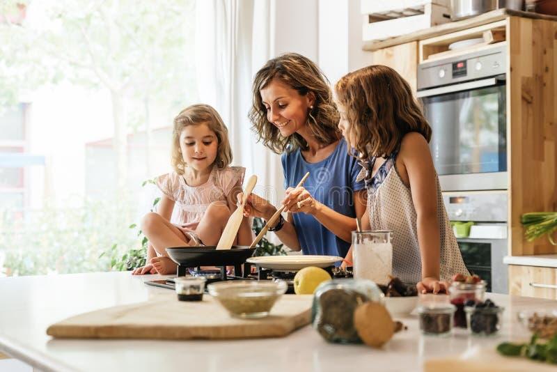 Pequeñas hermanas que cocinan con su madre en la cocina fotografía de archivo