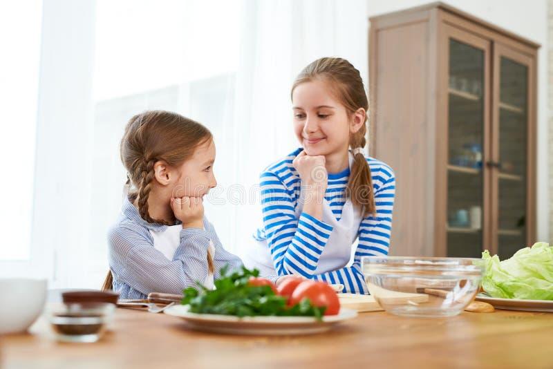 Pequeñas hermanas que discuten el menú festivo imagen de archivo libre de regalías