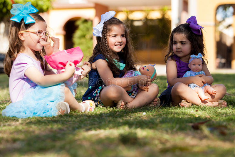 Pequeñas hermanas que juegan con las muñecas fotografía de archivo libre de regalías