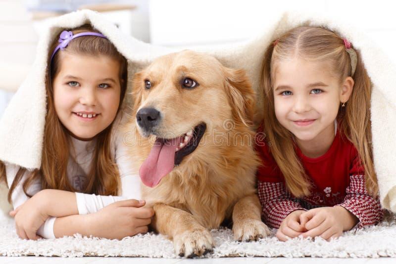 Pequeñas hermanas que se divierten con el perro casero fotografía de archivo libre de regalías