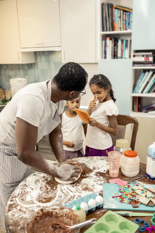 Pequeñas hijas que miran la historieta en la tableta mientras que padre que cocina la empanada imagen de archivo