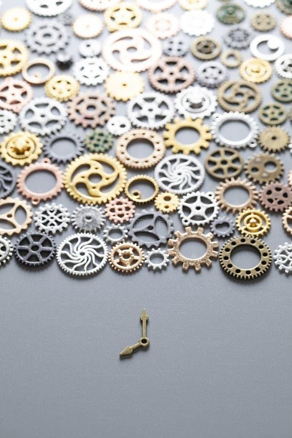 Pequeñas manos de reloj y muchos engranajes en un fondo gris foto de archivo
