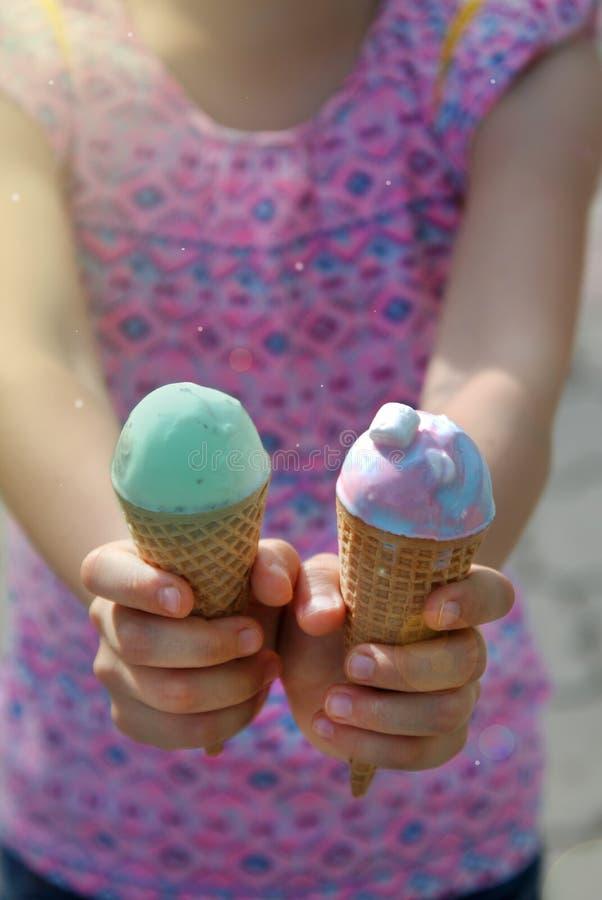 Pequeñas muchachas bonitas que sostienen dos conos de helado en manos Conos de helado azulverdes Adultos jovenes imágenes de archivo libres de regalías