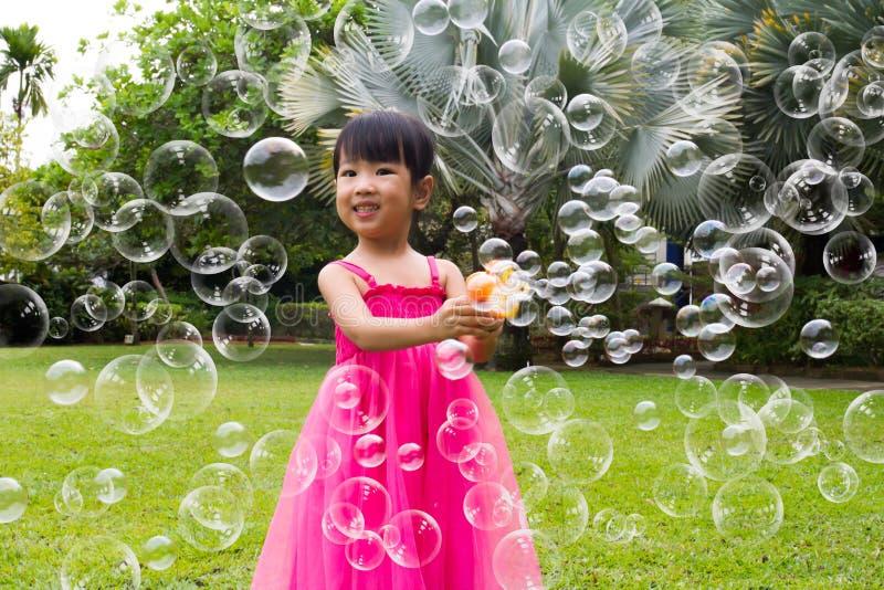 Pequeñas muchachas chinas asiáticas que tiran burbujas del ventilador de la burbuja imágenes de archivo libres de regalías