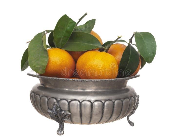 Peque?as naranjas, mandarinas, con las hojas en el cuenco del esta?o del vintage, aislado en blanco foto de archivo