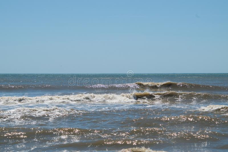 Pequeñas ondas de fractura en una playa con agua marrón oscura del océano imagen de archivo