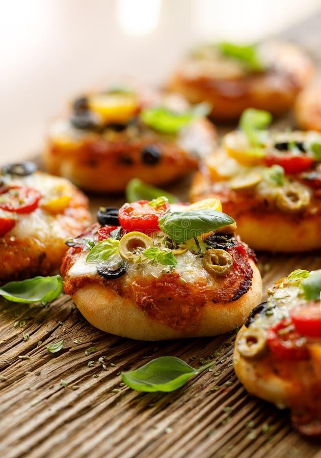 Pequeñas pizzas con la adición de los tomates de cereza, de las aceitunas, del queso de la mozzarella y de la albahaca fresca en  fotografía de archivo