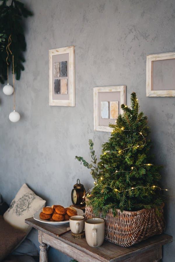 Pequeño árbol de navidad real con las luces de la Navidad amarillas, sitio de diseño moderno del estilo del desván en colores cla fotos de archivo