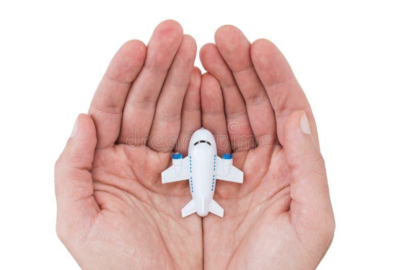 Pequeño aeroplano blanco del juguete en manos humanas imagenes de archivo