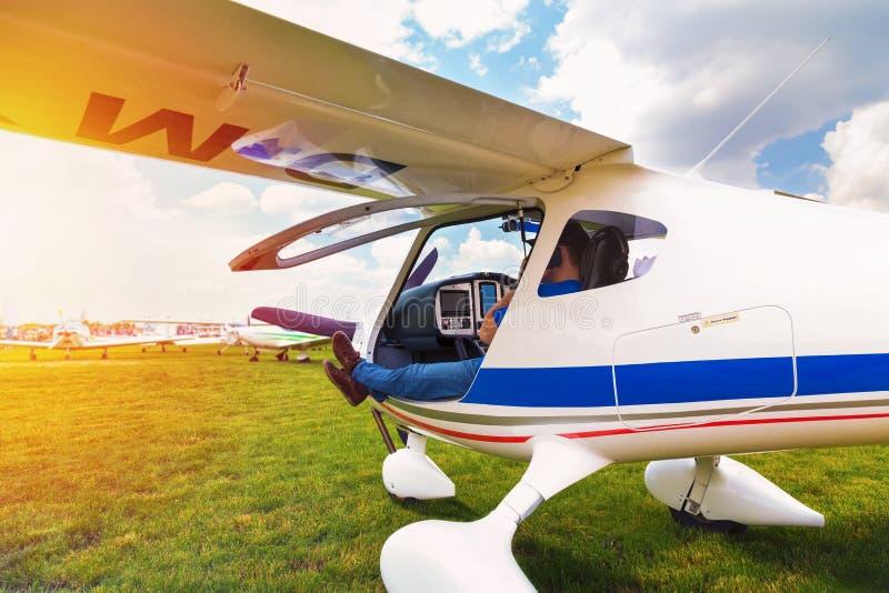 Pequeño aeroplano con el piloto a bordo que espera en campo imagenes de archivo