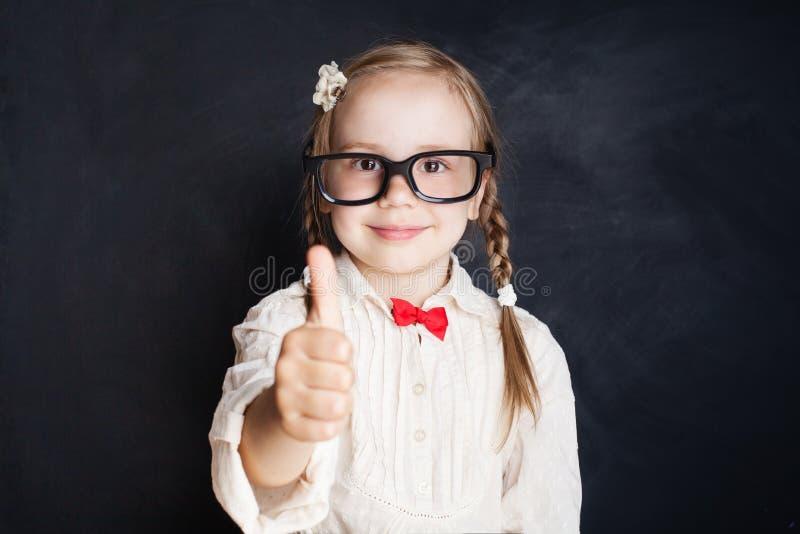 Pequeño alumno lindo de la colegiala que muestra el pulgar para arriba foto de archivo