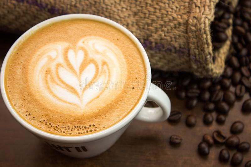 Pequeño arte del latte del tulipán con las habas y el saco del coffe imagen de archivo