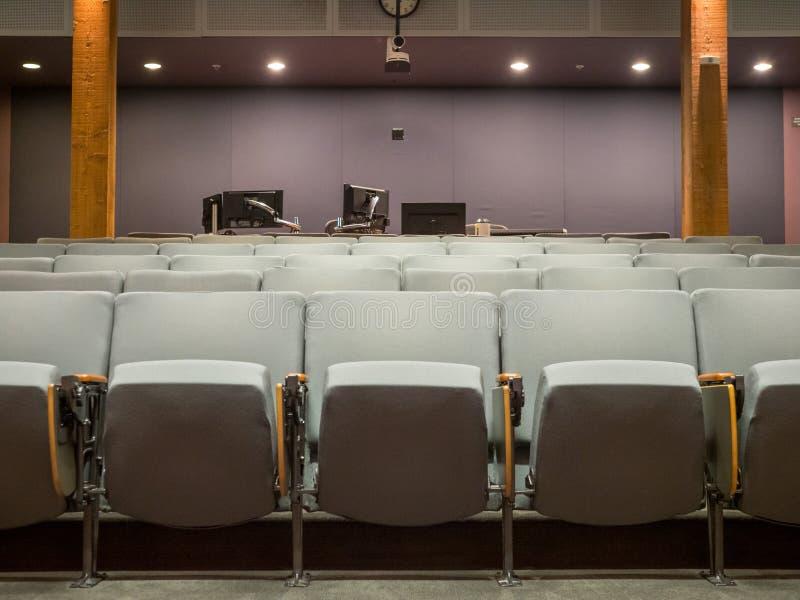 Pequeño auditorio de la oficina con las sillas grises y disposición del monitor de computadora en parte posterior fotografía de archivo libre de regalías