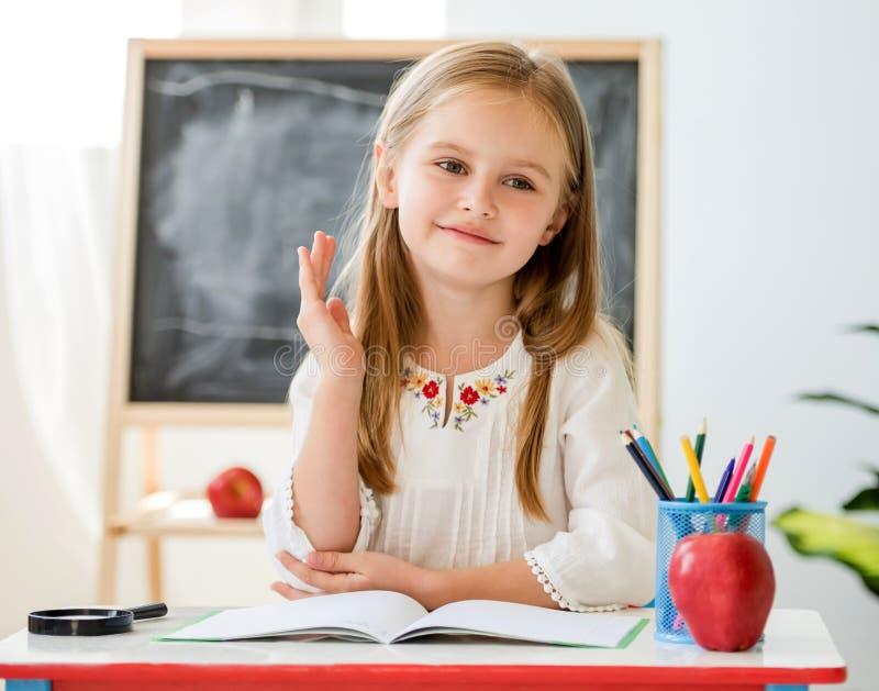 Pequeño aumento rubio de la muchacha una mano para la respuesta que se sienta en el escritorio en la sala de clase de la escuela fotografía de archivo